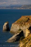 The diverse landscape of the Taranaki region of New Zealand features coastal cliff faces and high plains.