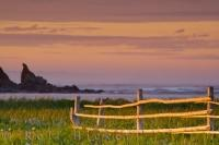 Taken in the town of L'Anse aux Meadows this picture shows the coastal scenery of the Atlantic Ocean and the rugged islands at sunset, as well as a rustic handmade fence in the foreground. This town is on the Northern Peninsula of Newfoundland.