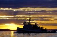 A commercial fishing boat traveling home off Northern Vancouver Island, glistens in the extraordinary colors of a stunning sunset.