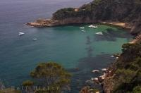 The azure waters of the Mediterranean Sea lap at the coast of the Costa Brava in Catalonia, Spain.