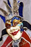 A costumed and masked character smiles into the camera beside the Grand Canal in Venice, Italy. Carnival season in Venice is an annual event and people dress in these elaborate costumes and masks and party in this city on water.