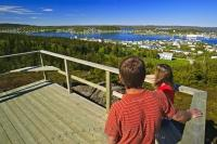 A couple enjoy a hike on a beautiful summer day ending at a platform overlooking the town of St Anthony in west Newfoundland.