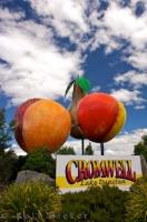 A brightly colored fruit sculpture and a sign reading Cromwell, Lake Dunstan welcomes visitors to this unique town in Central Otago, New Zealand.