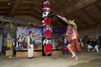 Dancer wearing a Traditional Mask in front of a Totem Pole on Vancouver Island B C
