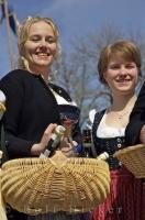 Two cute girls at a Bavarian festival in Putzbrunn, Southern Bavaria carrying baskets of drinks.