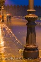 A street lamp illuminates the details of its own decorative post as well as the surrounding street scene during a heavy rainfall at the Piazza del Duomo in Pisa, Tuscany, Italy, Europe.