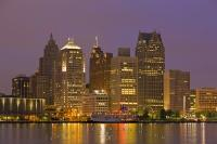 The skyline of Detroit City in Michigan USA is lit up at dusk with the lights of the buildings of offices and homes along the waterfront. This view is taken from the waterfront of Windsor Ontario, which is located in Canada.