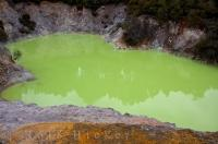 The luminous green water in Devil's Bath at the Wai-o-tapu Thermal Wonderland on the North Island of New Zealand is surrounded by the volcanic landscape.