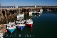 Brightly coloured fishing boats dock along the wharf at the marina in the town of Digby in the Evangeline Trail in the Bay of Fundy in Nova Scotia, Canada.