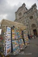 A souvenir stand selling postcards and prints stands outside the Basilica di Santa Maria del Fiore, the Duomo (Cathedral) of Florence, located in the Piazza di San Giovanni, in Florence, Tuscany, Italy.