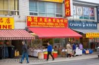A few early morning shoppers head to Chinatown in Toronto, Ontario to pick up the best deals and browse through the racks of clothes on display.