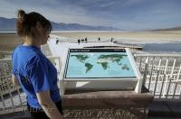 A woman checks out a sign showing the earths lowest points one being the Badwater Basin in Death Valley in California.