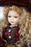 An elaborate and elegant porcelain doll features pretty long curly hair and victorian style clothing.