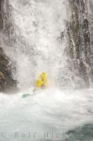 A kayaker takes a nose dive while waterfall running, an extreme water sport.