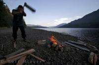 Tourist at work chopping firewood for a campfire at Nimpkish Lake outside of Port McNeill in British Columbia.