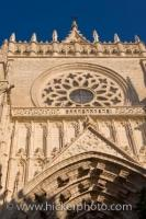The beautiful stone facade of the Seville Cathedral towers above your head as you go through the entrance in the Santa Cruz District in the City of Seville, Province of Sevilla, Andalusia, Spain. The Cathedral is a UNESCO World Heritage Site.
