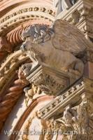 A lion with wings and other elaborate and complicated details can be seen on the facade of the Siena Duomo, the cathedral, in the historic old town district of the City of Siena - designated a UNESCO World Heritage Site in Tuscany, Italy.
