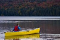 A popular form of outdoor recreation at Algonquin Provincial Park is paddling a canoe along the scenic shores of Rock Lake, surrounded by the stunning colors of fall.