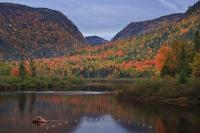 Jacques Cartier River in Quebec, Canada winds its way through the fall colored landscape as the lighting at sunset highlights the trees.