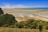 The curves of a sweeping bay namely Golden Bay, is fringed by native bush at Farewell Spit at the north-western tip of the South Island in the Tasman Region of New Zealand.