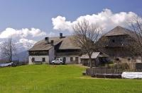 A farmers house sits upon the beautiful countryside in South Tirol, Italy with the Dolomite mountains in the background.