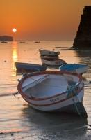 A romantic vacation scene with small wooden fishing boats during a colorful sunset in Cadiz, Spain.