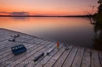 A beautiful sunset over a wooden wharf and fishing tackle and equipment at Lake Audy in Riding Mountain National Park, Manitoba Canada.