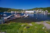 Deep blue skies and green hillsides surround the harbour of the town of Fleur De Lys along the Dorset Trail on Highway 412 in Newfoundland, Canada.