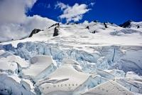 At the summit of the Fox Glacier on the South Island of New Zealand, the scenery is stunning as the sunlight reflects off the snow and ice under the deep blue colored sky.