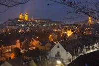 An aerial picture over the rooftops of homes and of the Freisinger Dom at dusk as the city of Freising is illuminated by street lighting on a cool winter evening.