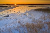 A beautiful close to an icy cold day as the sun settles on the horizon of a frozen lake at sunset  near the arctic community of Churchill, Manitoba.