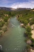 The green water of the Gallego River near Riglos in Huesca, Aragon in Spain flows past the ruins of an ancient bridge.