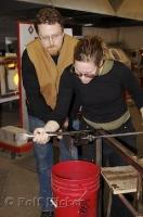 Two glass artist demonstration how glassblowing works at the Lincoln City Glass Center in Oregon, USA.
