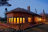 The golden lights at night at the Tuckamore Lodge in Main Brook, Newfoundland reflect across the peaceful landscape.