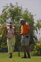 A man has a golf strategy for his partner at the Oliva Nova Beach and Golf Resort on the Costa Blanca, Valencia in Spain as she prepares to tee off.