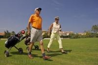 After two seniors were swinging their clubs, there is more exercise when pulling the golf cart at the eighteen hole course, the Oliva Nova Golf Course in Valencia, Spain in Europe.