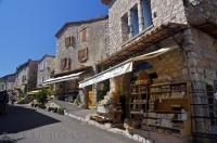 The sun shines down on the shops in the village of Gourdon in Provence, France in Europe.