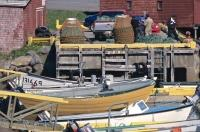 Fishing boats line the wharf of Grand Bank, Newfoundland as fishermen discuss business on the dock above amongst the crab pots.