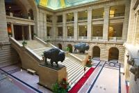 Two life sized bronze statues of North American bison flank the Grand Staircase in the Legislative Building, downtown Winnipeg, Manitoba, Canada. The building was completed in 1920.