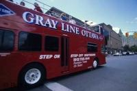 An open air double decker bus operated by Gray Line Ottawa in Ontario, takes passengers on a sightseeing tour through the city.