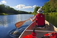 A canoer leisurely paddles down the scenic Mersey River, one of the many serene waterways located in the great outdoors of Kejimkujik National Park and National Historic Site in Nova Scotia, Canada.