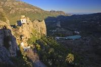 Shade closes in over the valley landscape and the Castle of Guadalest in the Province of Alicante in Comunidad Valenciana, Spain in Europe.