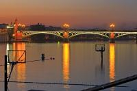 The night lights highlight the Puente de Isabel II bridge in the City of Sevilla in Andalusia, Spain and reflect off the calm waters of the Guadalquivir River.
