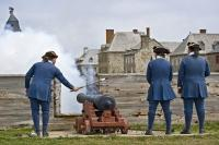 The cannon gun firing at the Fortress of Louisbourg in Cape Breton, Nova Scotia, demonstrated by the costumed military soldiers.
