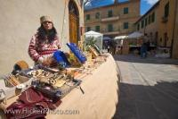 A handcraft stall at a market in the Piazza Galletti in the town of Pienza, Tuscany in Italy where an assortment of decorative items are displayed.