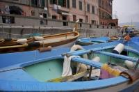 Colorful boats docked in the harbour of the Cinque Terre village of Vernazza in Italy below the waterfront walkway.