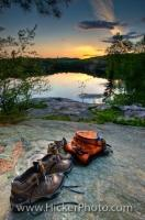 Two pairs of empty hiking boots and backpack sit on the rocky shores of George Lake, Killarney Provincial Park, Ontario, Canada. A top vacation destination in Ontario, Killarney Provincial Park is a treasure trove of natural wonders.