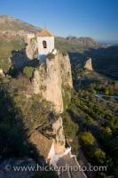 A historic church belfry perched atop a rockledge in the town of Guadalest in Comunidad Valenciana, Spain where visitors can look for miles across the scenic landscape.