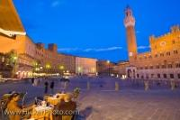 The historic old town district of Siena is one of the most popular parts of the city. In this picture the buildings are lit up at dusk as night falls on the city and people enjoy the twilight at some of the outdoor cafes.