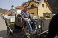 A man sits in the coachman seat on a horse and buggy ride surrounded by historic buildings in the village of Karlstein in the Czech Republic.